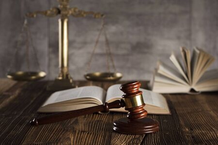 Judge antique gavel. Law symbols. Legal office. Wooden rustic table and stone background. Stock Photo