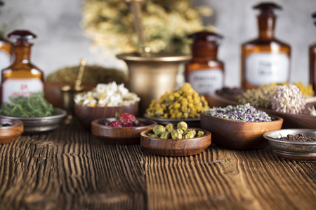 Natural medicine background. Brass mortar, scale. Rustic table. Assorted dry herbs in bowls. Bokeh.