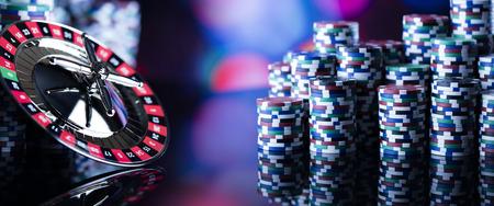 Casino thema. Hoog contrastbeeld van casinoroulette en pokerfiches op een speeltafel, allemaal op kleurrijke bokeh-achtergrond.