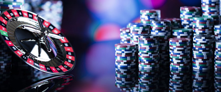 Casino theme. High contrast image of casino roulette and poker chips on a gaming table, all on colorful bokeh background.