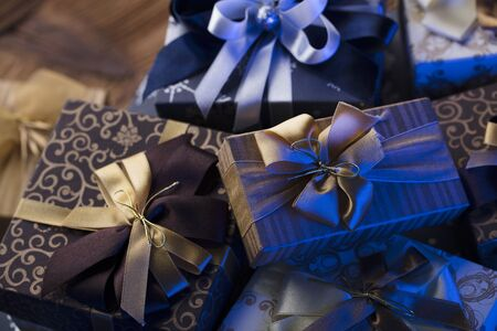 Presents in blue and gold aesthetics, rustic wooden table. Place for text.