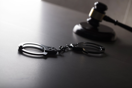 Criminal law concept. Cuffs and jugde gavel on stone background.