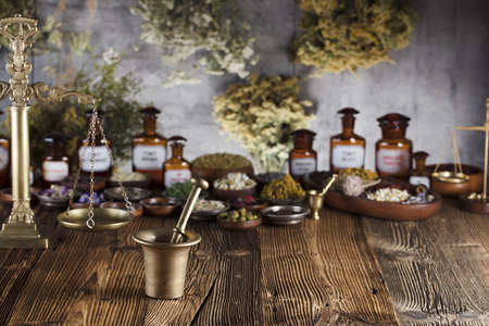 Natural medicine background. Brass mortar, bottles and scale. Rustic table. Assorted dry herbs in bowls. Bokeh.