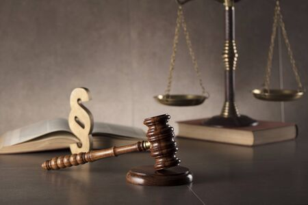 Judge antique gavel,scale, book and paragraph sign on stone background.