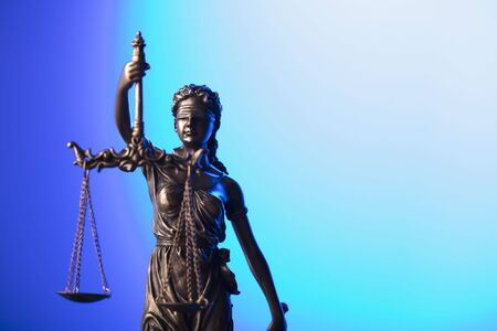 Law and justice concept. Themis statue on blue background. Stock Photo