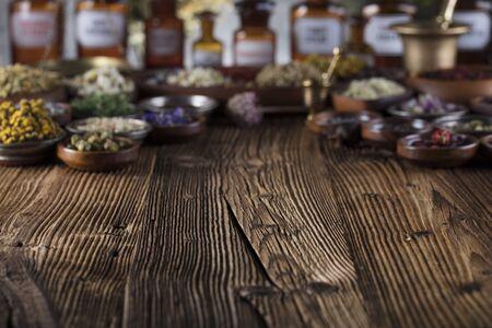 Alternative Medizin. Kräuter in Schalen, Mörser und Medizinflaschen auf rustikalem Holztisch.