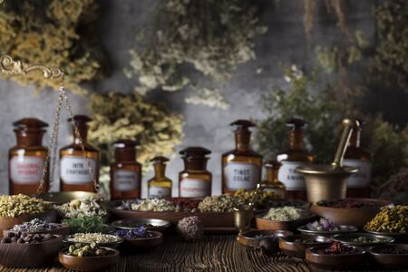 Natural medicine background. Brass mortar, bottles. Rustic table. Assorted dry herbs in bowls. Bokeh.