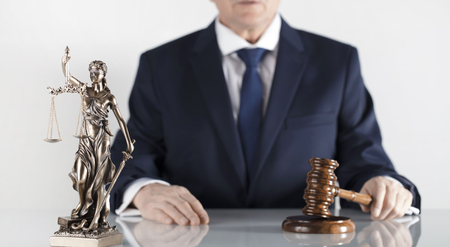 Legal counsellor. Mallet and Themis statue on white table and background.