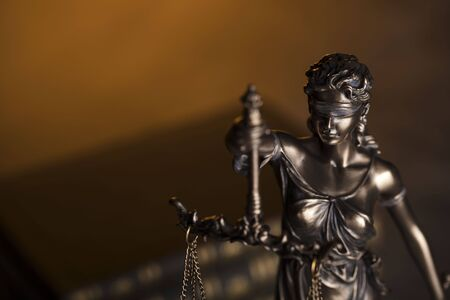 Law code. Statue of justice and  books. Brown background. Place for text.