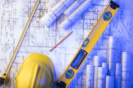 Contractor concept background. Rolls of blueprints, libela and helmet of constructor. Place for text. Foto de archivo
