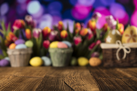 Easter theme. Easter eggs. Colorful tulips. Rustic wooden table. Shallow depth of focus. Bokeh background.