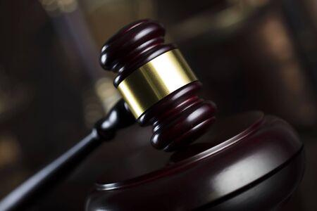 Law theme. Judge antique gavel. Bookshelf background.