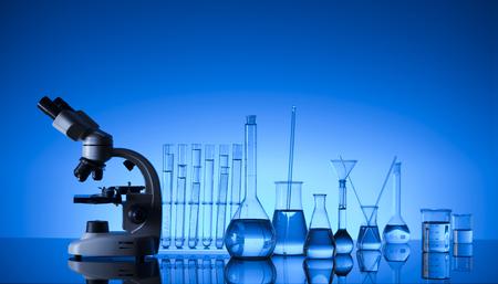 Laboratory concept. Science experiment. Laboratory glassware, microscope. Blue background. Archivio Fotografico