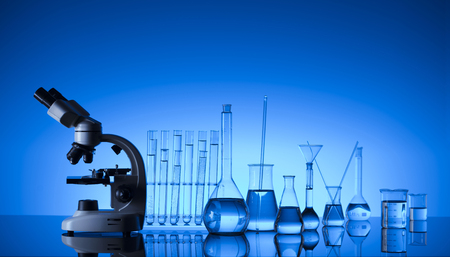 Laboratory concept. Science experiment. Laboratory glassware, microscope. Blue background. Imagens
