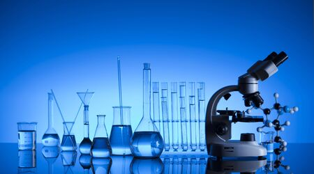 Laboratory concept. Science experiment. Laboratory glassware, microscope. Blue background. Stok Fotoğraf