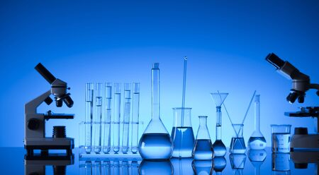 Laboratory concept. Science experiment. Laboratory glassware, microscope. Blue background. Stock Photo