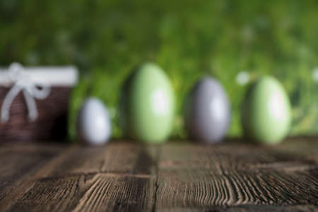 Easter background. Rustic wooden table. Easter basket with eggs. Green bokeh background. Place for text. Banco de Imagens