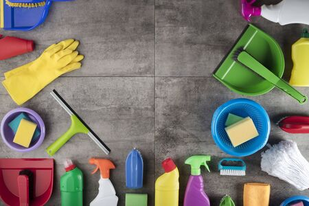 Spring cleaning concept. Colorful cleaning products on gray tiles. Place for typography.