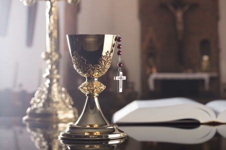 Holy communion concept. The Cross, Holy Bible, rosary and golden chalice