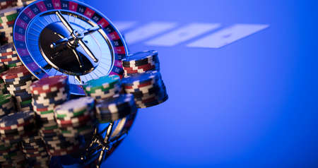 Gambling theme. Roulette and poker chips on blue background.