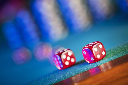 Gambling theme.  Dice and poker chips on color bokeh background.