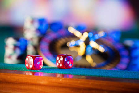 Gambling theme.  Dice, roulette wheel and poker chips  on color bokeh background. Stock Photo