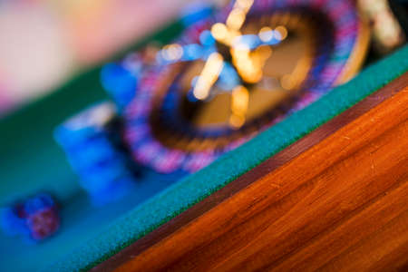 Gambling theme.  Dice, roulette wheel and poker chips on color bokeh background.