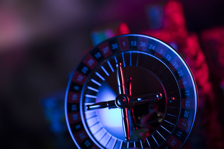 Gamling theme. Close up of roulette and stack of chips. Blue light.  Bokeh background.