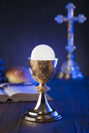 First holy communion theme. The Cross, Holy Bible, rosary and golden chalice. Bread and grapes – symbols of Christianity. Stock Photo