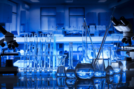 Science concept background. Chemical experiment. Beakers and microscope in laboratory.