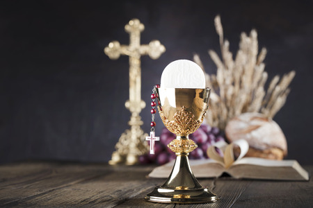First holy communion theme. The Cross, Holy Bible, rosary and golden chalice. Bread and grapes – symbols of Christianity.