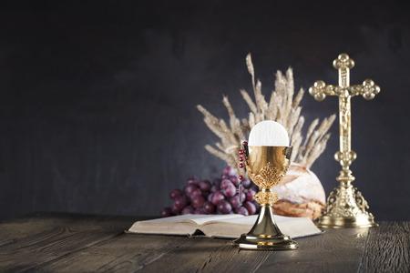 Tema de la primera comunión. La Cruz, Santa Biblia, Rosario y Cáliz de oro. Pan y uvas: símbolos del cristianismo. Foto de archivo