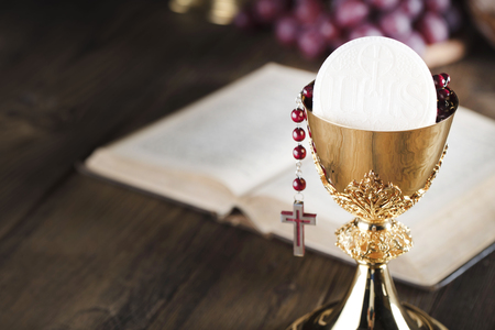 First holy communion theme. Bible, rosary and golden chalice. Bread and grapes – symbols of Christianity.