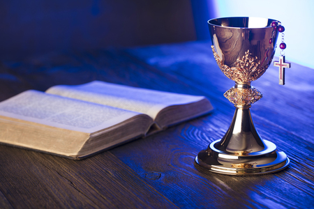 Roman Catholic Church theme. The Cross, Holy Bible and golden chalice on brown wooden table.