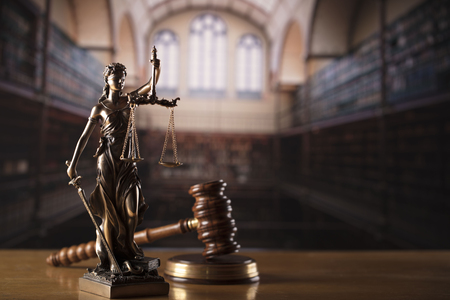 Law and justice theme – court library. Gavel and Themis statue.