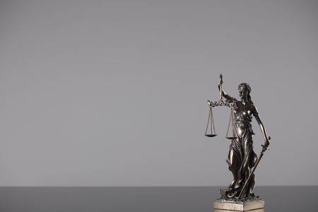 Law theme – statue of justice on gray background.