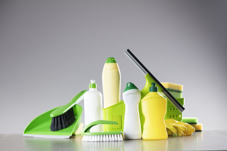 House and office cleaning up theme.  Set of colorful cleaning products on gray background.