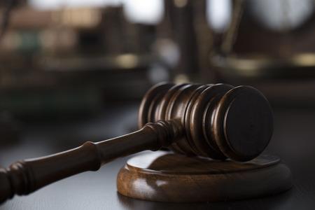Antique gavel on the law symbols background.