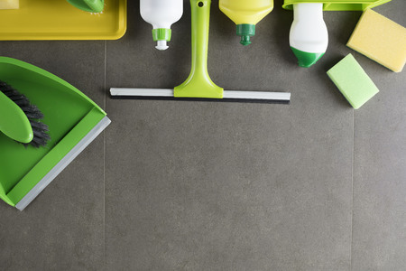 House and office cleaning up theme.  Set of colorful cleaning products on gray background. Top view.