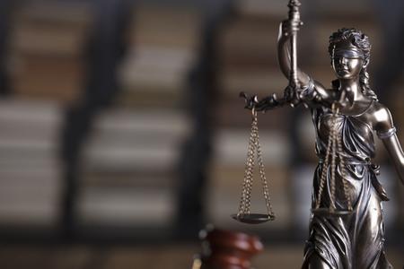 Advocaten kantoor. Themis en juridische boeken op houten bureau.