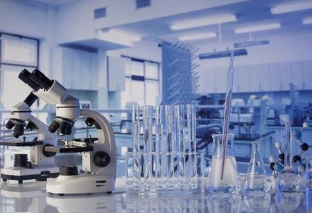 Modern scientific laboratory interior. Laboratory glassware and microscope on the glass table. Banco de Imagens