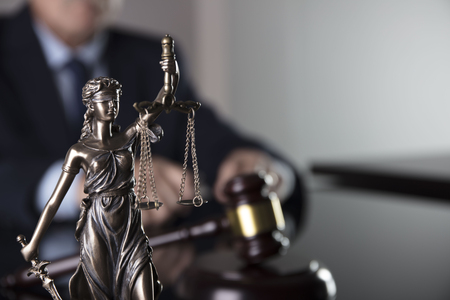 Consultation with a lawyer concept. Attorney at the office. Statue of justice, mallet and documents on the glass table. Stockfoto