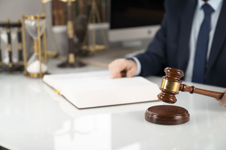 Lawyer concept background. Lawyer working at the office. Gavel and legal book on the white glass table.