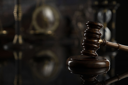 Courtroom concept. Law symbols composition. Gavel, balance and books. Brown background.