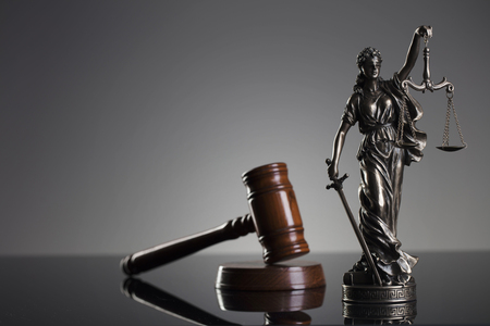 Law concept. Gavel of  the judge and statue of the justice. Gray background. Stock Photo