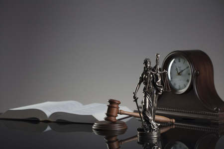 Law concept. Gavel of  the judge, statue of the justice and legal book. Gray background. Stock Photo