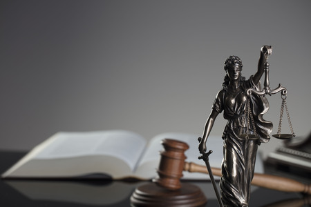 Law concept. Gavel of  the judge, statue of justice and legal books. Gray background. Stock Photo
