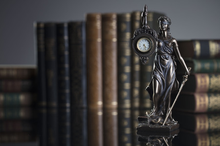 Law concept. Themis -  statue of justice and legal books. Gray background.