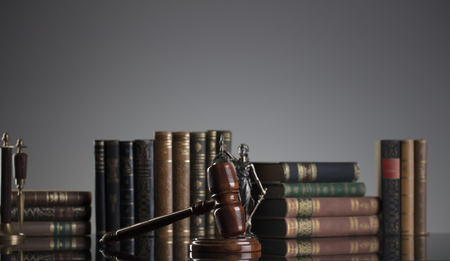 Law concept. Statue of justice and legal books. Gray background. Stock Photo