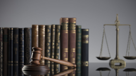 Law concept. Gavel of  the judge, scale of the justice and legal books. Gray background. Stock Photo